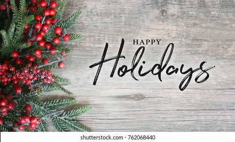 Happy Holidays Text with Holiday Evergreen Branches and Berries in Corner Over Rustic Wooden Background - Shutterstock ID 762068440