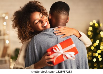 Happy holidays. Thankful afro woman with christmas gift hugging husband at home