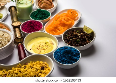 Happy Holy concept  showing Indian assorted lunch food like paneer butter masala, naan, jeera rice, black chana fry, jalebi, fujiyama, thandai and Farsan with holi colours and pichkari