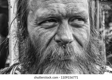 Happy homeless beared old man closeup portrait in black and white