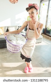 Happy homemaker wife carrying basket with the laundry smiling into the camera