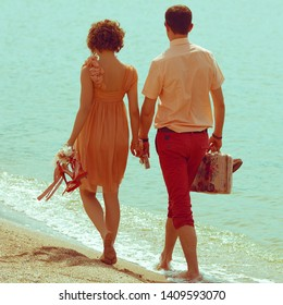 Happy honeymoon concept. Young happy married couple walking around at the seaside holding each other and their shoes. Sunny summer day. Outdoor shot