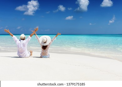 Happy honeymoon couple in summer clothing enjoys their vacation time on a tropical beach
