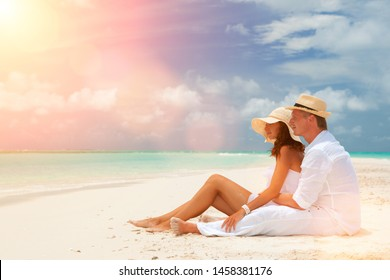 Happy honeymoon vacation at summer. Couple relax on the white sand of beach. Happy sea lifestyle. Young family, man and woman rest on the beach of ocean. Couple in love travel to island. Love travel