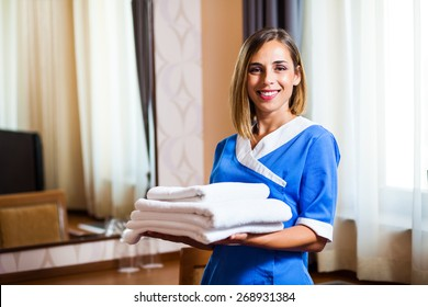 Happy hotel maid holding towels