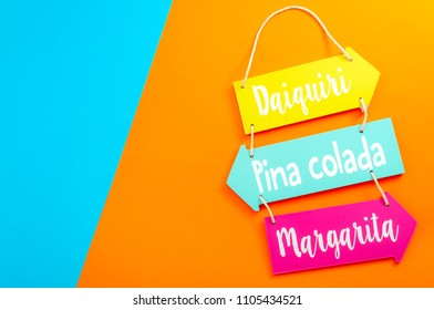 Happy hour, alcohol and summer vacation drinks concept with a wooden menu sign for daiquiri, margarita and pina colada cocktails isolated on minimalist orange and blue background with copy space