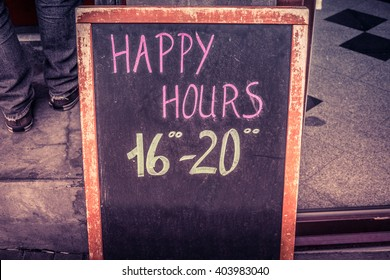 Happy hour board with text written in chalk