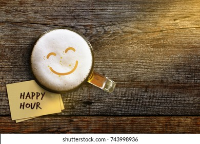 Happy Hour Concept for Bar, Cafe or Night club to Promote a Special Offer, Smiley Face on Foam in Glass of Beer over Wooden Table and Sticky Note, Top View