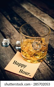 happy hour with label on paper note. Glass of scotch whiskey