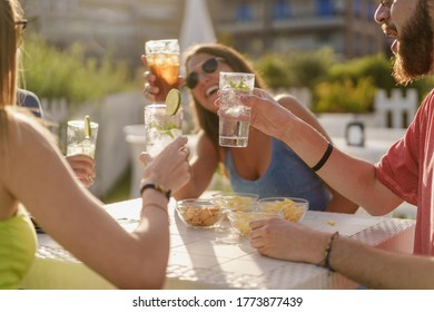 Happy hour toasting. Young friends clinking with fresh mojitos sitting in a counter restaurant and taking aperitif in the summer. Friendship and togetherness concept