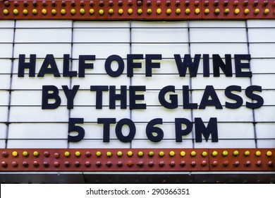 Happy hour in a tourist town: Daily bargain on wine announced on a vintage movie marquee on a main street in America