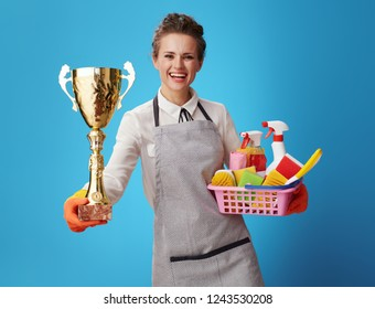 happy housemaid in apron with basket with detergents and brushes showing gold goblet against blue background. Cleaning service number one! housemaid is proud of her job recognition and customer trust