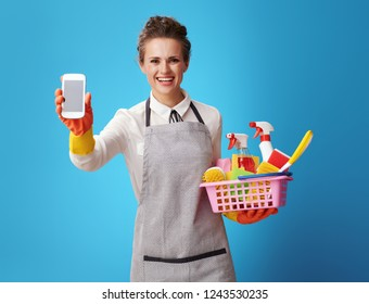 happy housemaid in apron with basket with detergents and brushes showing cellphone blank screen isolated on blue background. One call to cleaning service experts and cleanliness guaranteed