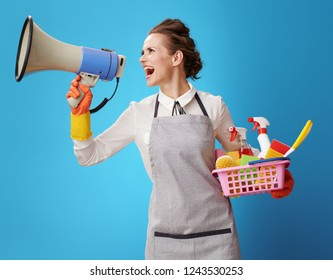 happy housemaid in apron with basket with detergents and brushes shouting through megaphone isolated on blue. Attention! - Simple and trouble-free cleaning service from skilled cleaners.
