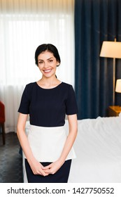 happy housemaid smiling while looking at camera in hotel room