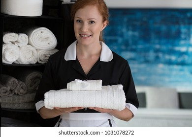 Happy housemaid with white towels. Domestic cleaning service concept