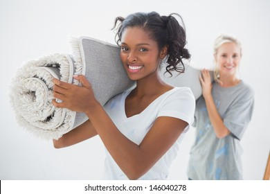 Happy housemates carrying rolled up rug looking at camera in new home