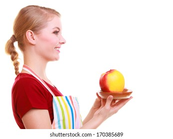 Happy housewife or chef in colorful kitchen offering red yellow apple healthy fruit isolated studio shot. Diet and nutrition.