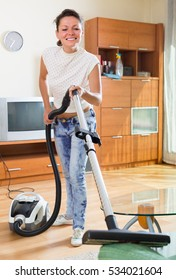 Happy housewife cleaning apartment with vacuum cleaner and smiling