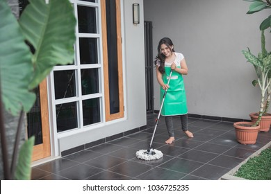 Happy housewife cleaning the floor with mop in the terrace