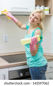 Happy housewife cleaning in the kitchen.