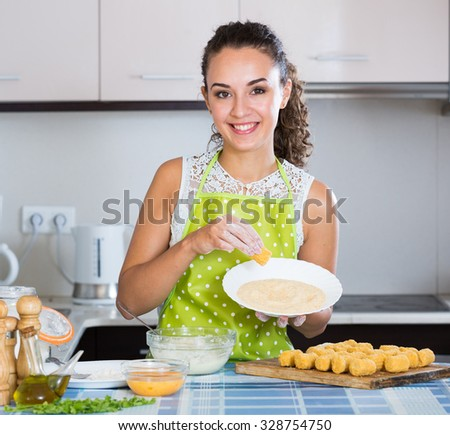 Happy housewife cooking breadcrumbed croquettes in domestic kitchen