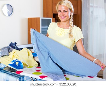 Happy housewife ironing clothing at home interior