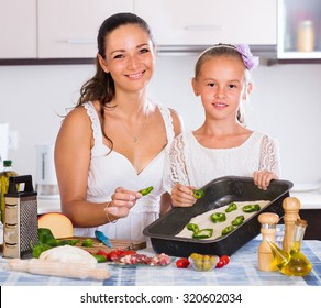 Happy housewife with little girl cooking Italian pizza  indoors