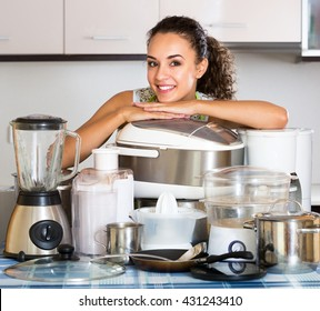 Happy housewife with multicooker and other culinary appliances at home
