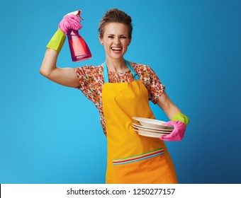 happy housewife in orange apron with washed plates showing dishwashing detergent isolated on blue background. red dishwashing detergent in transparent bottle in housewife hand in protective gloves