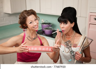 Happy housewife shows her smoking friend a dish in the kitchen