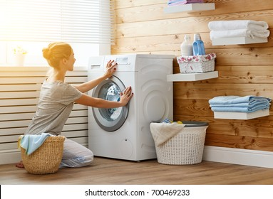 a Happy housewife woman in laundry room with washing machine