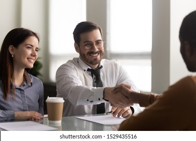 Happy hr manager sitting with smiling female colleague at table in office, shaking hands with african american male employee, welcoming at new job. Recruitment, employment, hiring process concept.