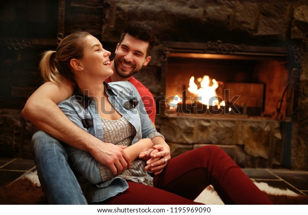 Happy hugging couple enjoying in mountain house near fire from fireplace