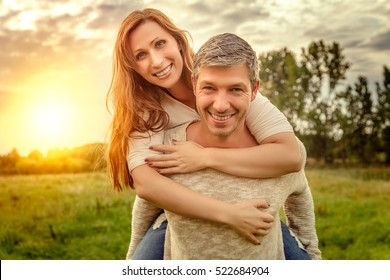 happy hugging couple with sun behind