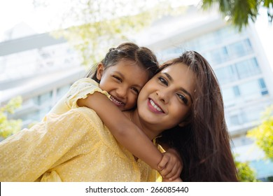 Happy hugging Indian mother and daughter