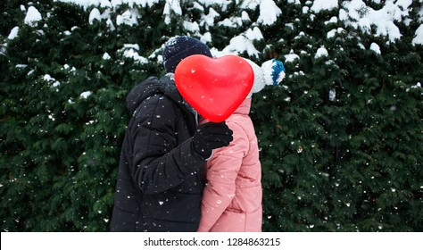 happy hugging and kissing couple in warm winter clothes is standing outdoors with a heart shaped red balloon on the green fence background