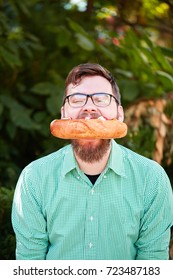 Happy, hungry bearded hipster man biting a big fresh spicy hot dog on a blurred natural background. Good fast food sevice. Copy space.