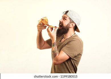 Happy hungry man eating pizza from a box isolated on white background. Handsome sexy bearded young man hipster with long beard and mustache on serious hairy face eating pizza.