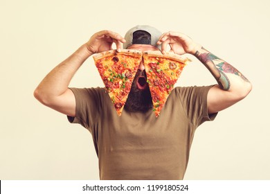 Happy hungry man eating pizza. Bearded man holds two pieces of pizza in his hands.