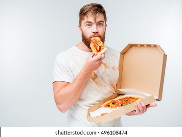 Happy hungry man eating pizza from a box isolated on white background