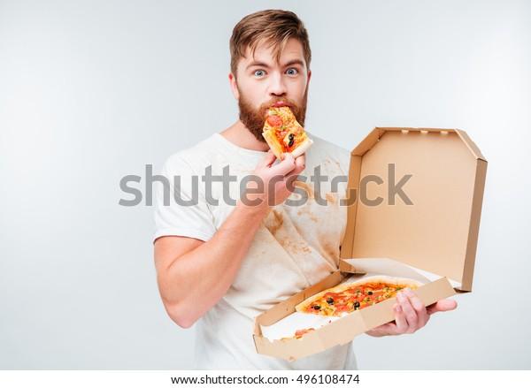 Feliz hombre hambriento comiendo pizza de una caja aislada de fondo blanco
