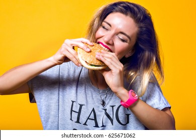 Happy hungry moments of pretty young woman with pink lipstick enjoying tasty hamburger isolated on yellow background. Stylish american model eating burger with closed eyes, following fastfood