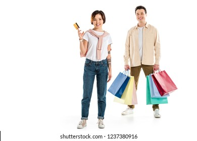 happy husband holding shopping bags while wife presenting credit card