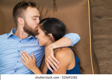 Happy husband kissing his wife lying on couch