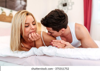 Happy husband loving wife while  lying in bed