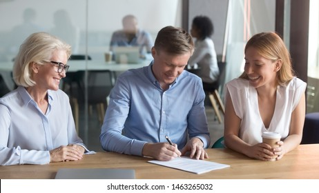 Happy husband put signature on contract buy first house from realtor together with excited young wife, overjoyed couple tae loan sign agreement after successful meeting with female banker or realtor