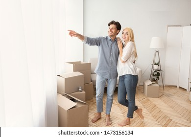 Happy Husband Showing Wife The View From Window Of Their New Home. Moving Apartment Concept. Copy Space