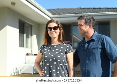 Happy husband and wife (age 35-45) standing in front of their new home. Buy, sell, real estate, property, home insurance, mortgage, bank loans and housing market concept. Real people. Copy space