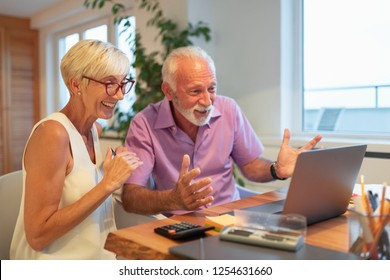 Happy husband and wife reading bank documents at home.